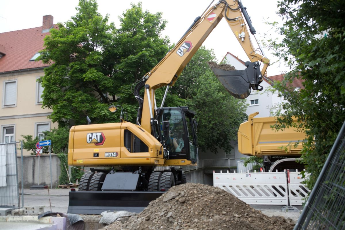 M314 Wheeled Excavator unloading truck to backfill