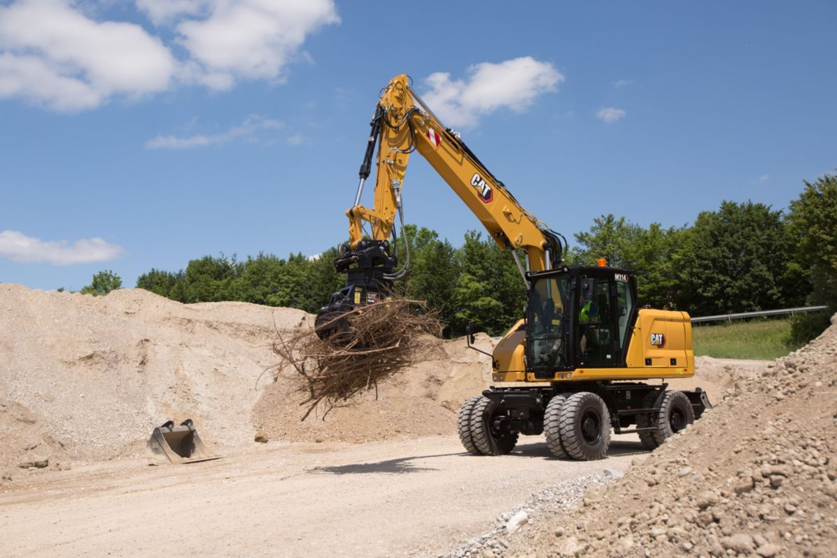 M314 Wheeled Excavator moving debris with grapple